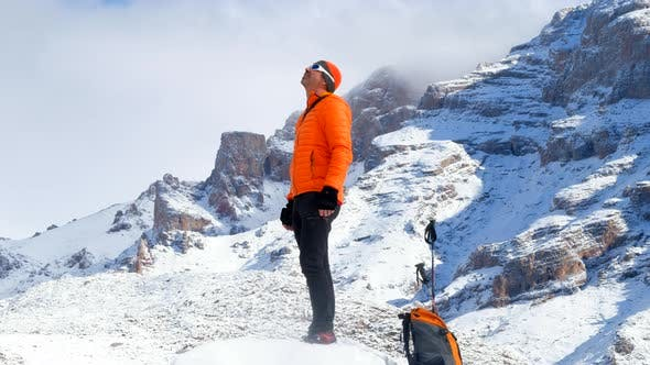 Cover Image for Man Stands On Snowy Mountain Peak