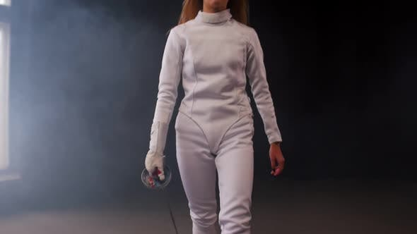 Thumbnail for A Young Woman Fencer Putting the Sword Behind Her Shoulders in the Studio