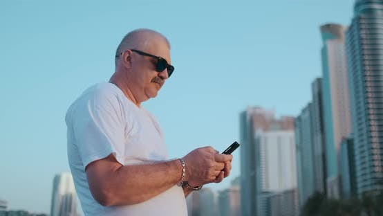 Cover Image for Mature Senior Man Walking Texting on Cell Phone