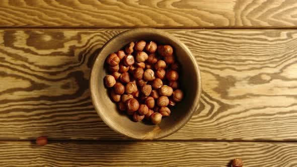 SLOW: Peeled Nuts Fall Into A Wooden Dish On A Table - Top View