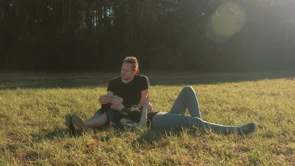 Thumbnail for Couple of Lovers Relax in the Park Lie on the Grass and Chat.