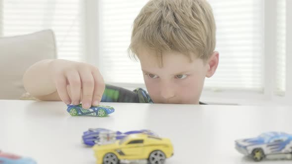 Thumbnail for Boy playing with toy cars