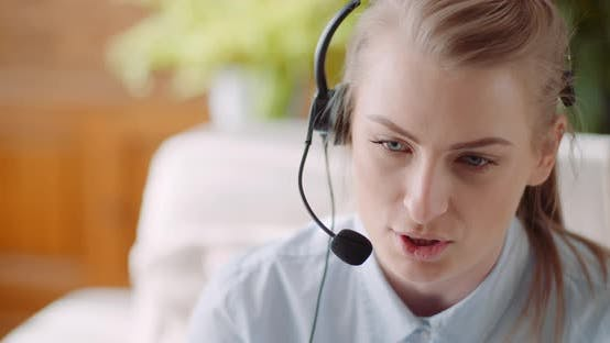 Thumbnail for Sales Representative in Headset Speaking To Client and Making Video Conference Call on Laptop