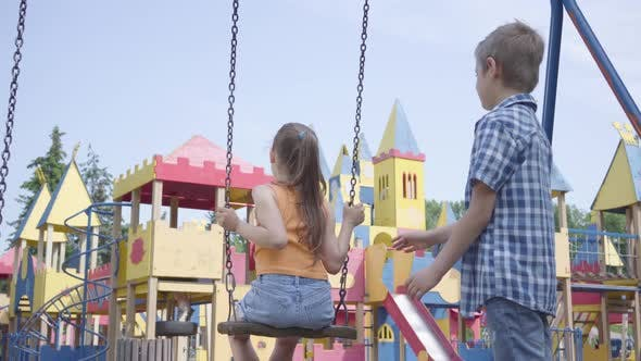 Thumbnail for Cute Boy Swinging on a Swing Beautiful Girl with Long Hair, Smiling. A Couple of Happy Children