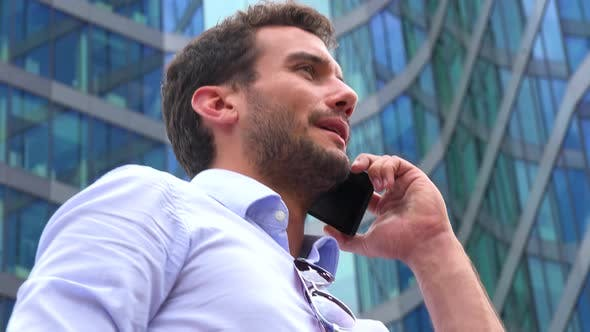 Thumbnail for A Young Handsome Businessman Talks on a Smartphone - Closeup From Below - an Office Building