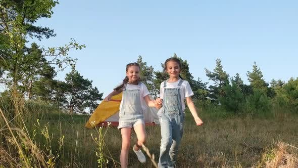 Two Little Girls Run Near the Campsite on a Summer Day