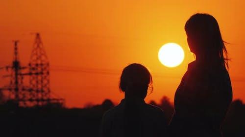 Mama und Tochter beobachten den Sonnenuntergang über dem urbanen Horizont