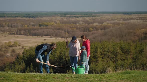 A Family of Volunteers Plants a Tree to Green the Planet