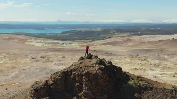 Photographer Man on Mountain Top. Iceland. Aerial View