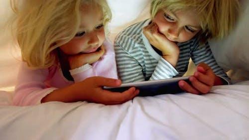 Geschwister mit digitaler Tablette unter Decke im Schlafzimmer zu Hause 4k