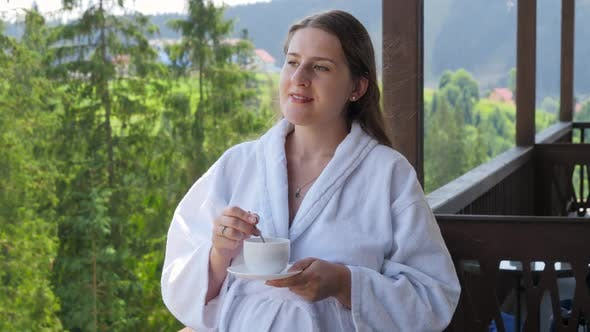 Portrait of Smiling Young Woman in Bathrobe Holding Cup of Coffee and Looking on Beautiful Mountains