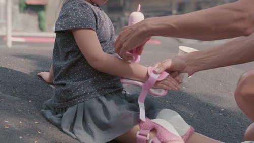 Little Girl Preparing for Roller-skating
