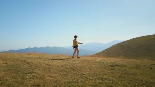 Hipster Woman Walk on Mountain Peak in Sunshine