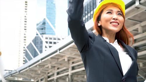 Young Asian Smart Engineer Looking Up the Sky with Success Gesture Over Building Cityscape
