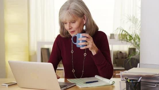 Thumbnail for Senior woman drinking coffee using laptop computer