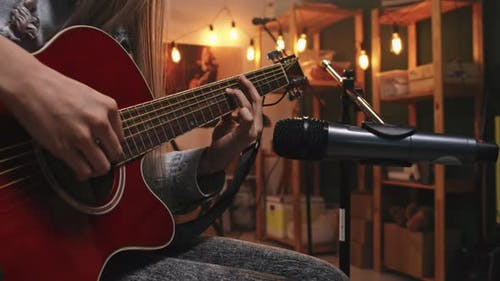 Female Guitarist Playing To Mic In Studio