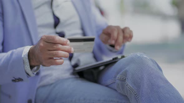 Cover Image for Man Using Tablet Pc and Holding Credit Card