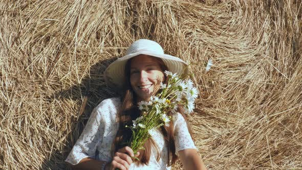 Cover Image for Cheerful Woman with Flowers Against Haystack