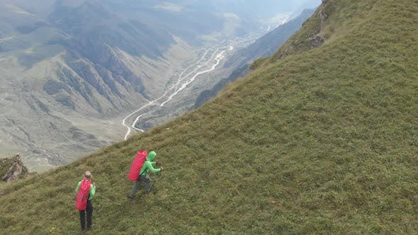 Thumbnail for Aerial Shot of a Group of Tourists with Backpacks Climb the Mountain