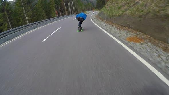 A skateboarder downhill skateboarding on a mountain highway road.