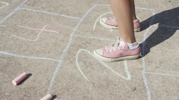 Thumbnail for Young girl playing Hopscotch at park, closeup of feet
