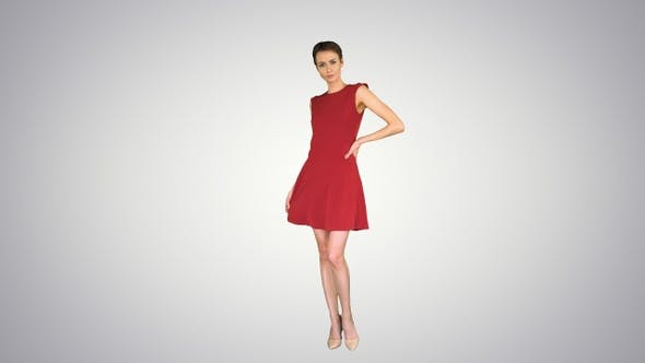Thumbnail for Girl in A Red Dress Posing, Straightens Her Dress on Gradient