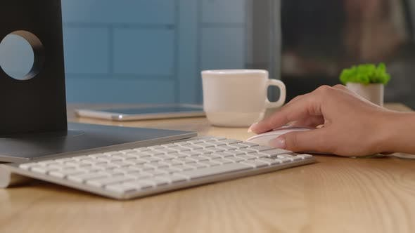 A Woman Controls a Computer Mouse and Typing on a White Keyboard Sitting at an Office Table or at