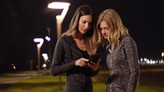 Thumbnail for Two attractive women timing jog with stop watch and smartphone outside at night
