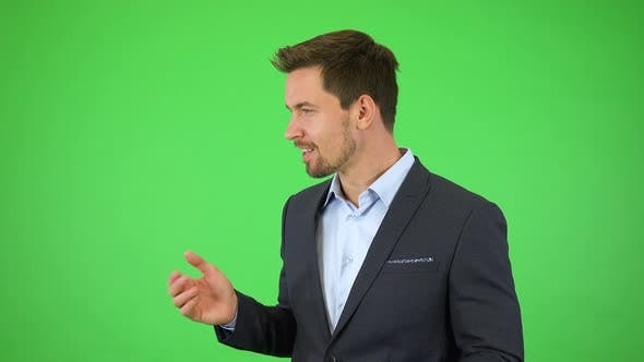 An Amazed Businessman Smiles and Points in Fascination at Objects Floating Around Him - Green Screen