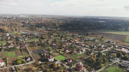 Aerial view of countryside with cloudy blue sky. Forest countryside with cottages and buildings