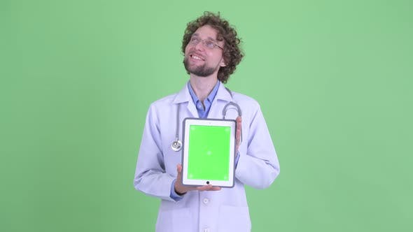 Cover Image for Happy Young Bearded Man Doctor Thinking While Showing Digital Tablet