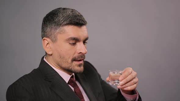 Thumbnail for Sad Businessman Drinking Shot of Vodka at Restaurant, Strong Alcoholic Drink
