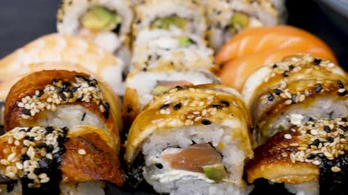 Traditional Japanese Sushi Rolls on Black Stone Plate