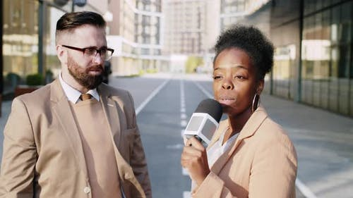 Black Female Journalist Interviewing Caucasian Businessman Outdoors