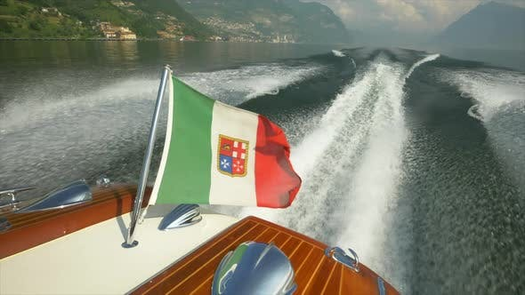 Thumbnail for A classic luxury wooden runabout boat with an Italian flag on a lake.