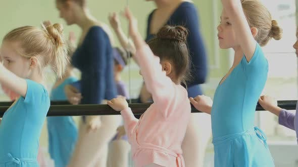 Female Ballet Dancer strides along the barre in the backgound encouraging the four young Ballerinas