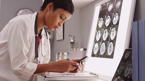 Thumbnail for Young attractive doctor texting results of brain scans