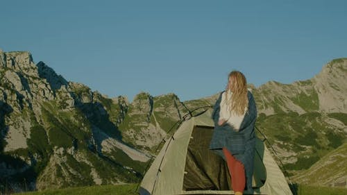 Happy travel woman with dreadlocks near the tent standing on top of hill looking at sunrise.