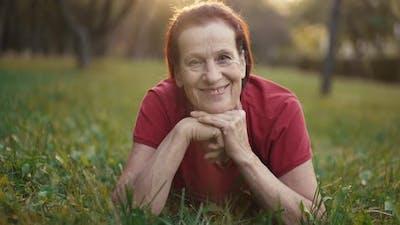 Elderly Happy Woman Lying on the Grass