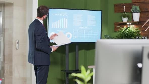 Thumbnail for Caucasian Businessman Standing Near a Big Screen TV