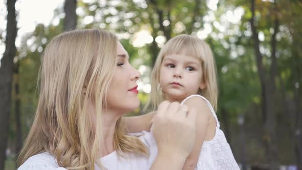 Thumbnail for Portrait of Young Blond Woman in White Dress Caressing Her Cute Daughter