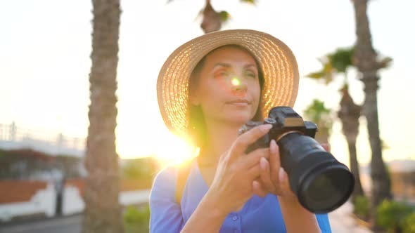 Photographer Tourist Woman Taking Photos with Camera in a Beautiful Tropical Landscape at Sunset