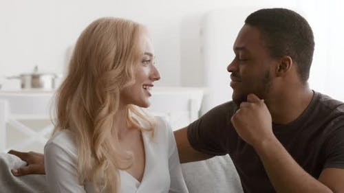Loving Black Husband Touching Wife's Chin Flirting Sitting At Home