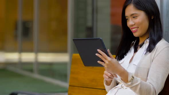 Thumbnail for Asian Woman with Tablet Computer Sitting on Bench
