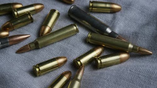 Cinematic rotating shot of bullets on a fabric surface