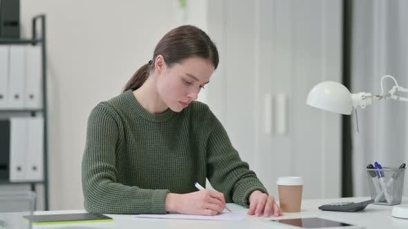 Thumbnail for Junge Frau schreibt auf Papier