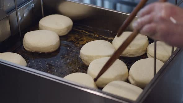 The Donuts Are Being Fried in a Deep Fryer