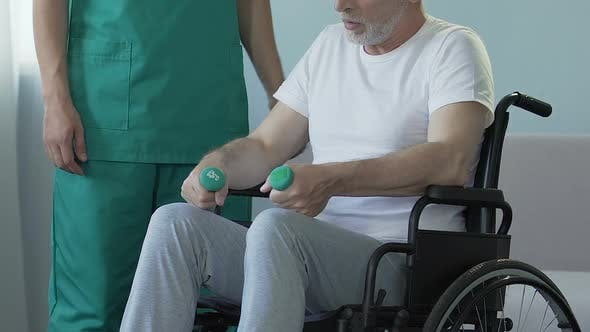 Thumbnail for Aged Man Sitting in Wheelchair, Holding Dumbbells, Talking to Nurse, Recovery