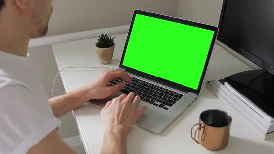 Over the shoulder shot of European millennial hipster man typing and looking at laptop green screen
