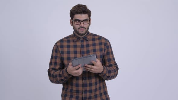 Thumbnail for Happy Young Bearded Indian Hipster Man Thinking While Using Digital Tablet